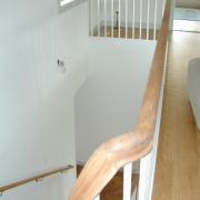 Böjlimmad trappa i ek. Vitlackade vangstycken och räckespinnar. Steg nr. ett som blocksteg.