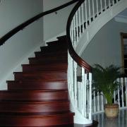 Böjlimmad trappa i mahogny med vitlackade vangstycken och räckespinnar