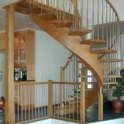 Svängd trappa i ek med ett underliggande vangstycke. Stående räckespinnar i rostfritt.