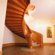 Elipsformad trappa i körsbär handledare i mässsing. Kantskodd matta på steg.