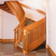 Elipsformad trappa i körsbär handledare i mässing. Kantskodd matta på steg.