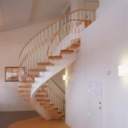 Svängd trappa med ett underliggande vangstycke, vit lack och ek.