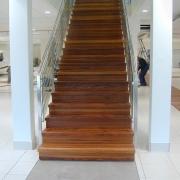 Rak trappa i ek med glasräcke och rostfria räckespinnar.