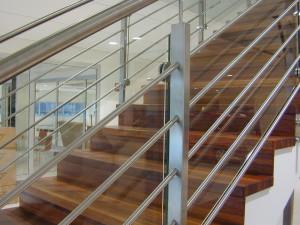 Rak trappa i ek med underliggande vangar. Räcke med rostfria stolpar och glas.