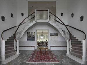 Böjlimmad dubbel trappa med kantskodd matta på steget, handledare i mahogny